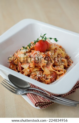 Traditional Italian pasta Bolognese topped with grated parmesan cheese sprinkled on a tomato based meat sauce garnished with thyme and cherry tomato - stock photo