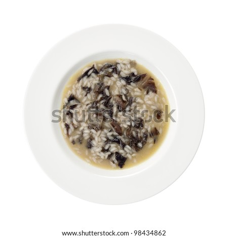 Traditional italian recipe red chicory and spinach rice on a round plate isolated on white background. Also known as Risotto Radicchio e Spinaci - stock photo
