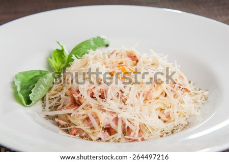 Traditional Italian spahgetti Pasta Carbonara with roasted bacon, pashshot egg  and parmesan cheese decorated with fresh basil and cherry tomatoes on white plate