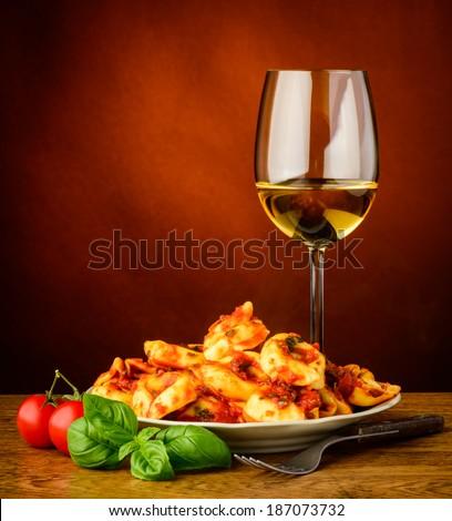 traditional italian tortellini pasta with tomato sauce, basil and white wine - stock photo