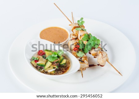 Traditional Japanese appetizer Kushiyaki - chicken skewers with vegetable salad and nut sauce on a white plate isolated