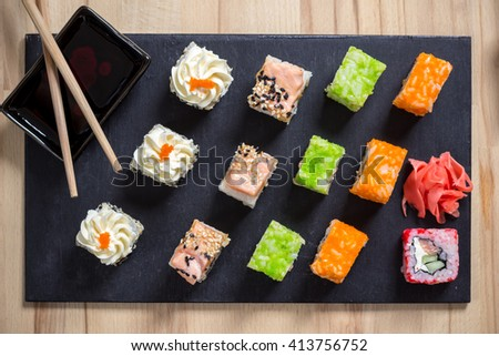 Traditional japanese food, Mix colorful sushi set on wooden  black board with chopsticks. Green, orange, red sushi rolls. Food photography. - stock photo