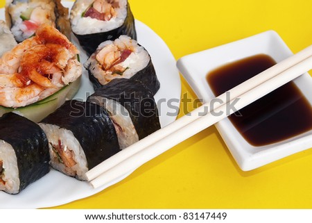 Traditional Japanese food Sushi. Chopstick, sushi on white plate and sauce on yellow napkin. Sushi collection. Traditional sushi. Delicious Sushi. Japanese food. Japanese sushi. Sushi set. Sushi Set.