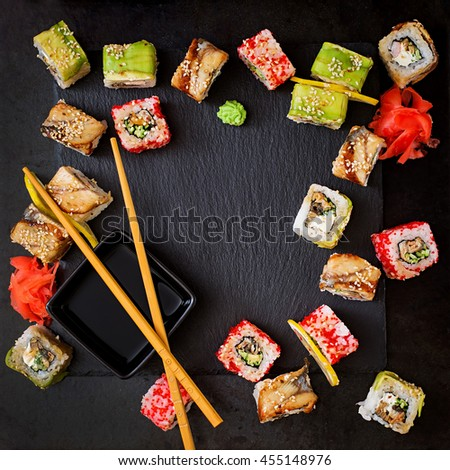 Traditional Japanese food - sushi, rolls and sauce on a black background. Top view