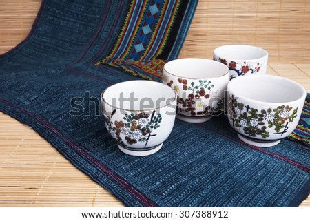 Traditional Japanese pottery on bamboo mat and brocade fabric