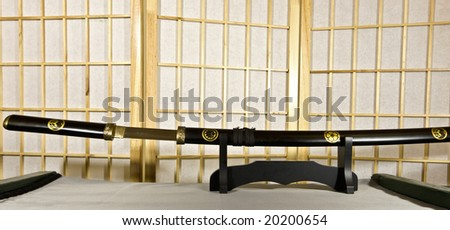 Traditional Japanese samurai sword mounted on special black wooden stand - stock photo