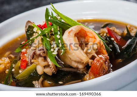 Traditional japanese soup with seafood, seaweeds and prawns - stock photo