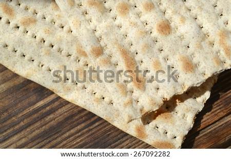 Traditional jewish bread matzo on wooden table - stock photo