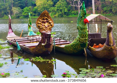 Traditional khmer boats with green parrot and a bird heads and Shiva deity carved bows at Bayon moat pier waiting for tourists - stock photo
