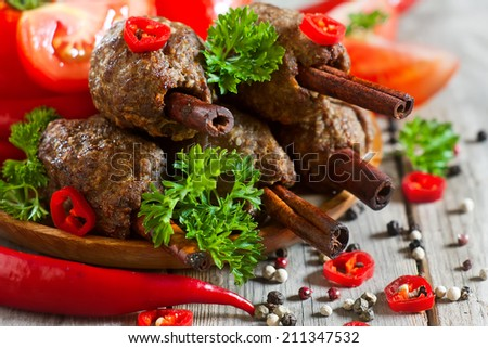 Traditional lamb kebab on cinnamon sticks on wooden plate with tomato, parsley and red hot pepper. Selective focus. - stock photo