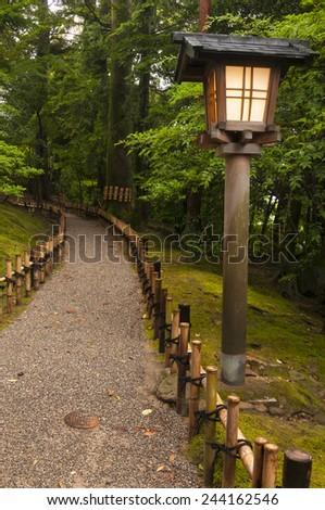Traditional lantern near the path in japanese garden - stock photo