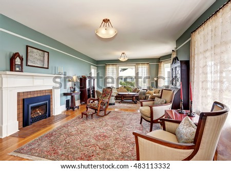 Traditional living room interior in blue and white tones, fireplace and rug. Northwest, USA