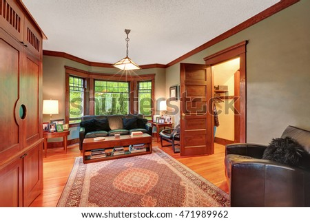 Traditional living room interior with black leather sofa set, hardwood floor, rug and large window with brown wooden trim. Northwest, USA