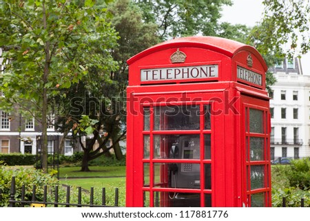 Traditional London symbol red public phone box on green park and residential district background, Great Britain - stock photo
