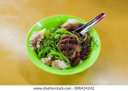 Traditional Malay chendol cold dessert served with coconut and red beans. - stock photo
