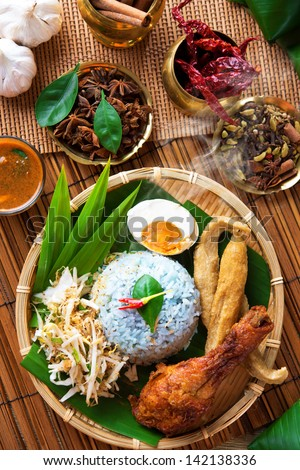 Traditional Malaysian food, Asian cuisine. Nasi kerabu is a type of nasi ulam, popular Malay rice dish. Blue color of rice resulting from the petals of  butterfly-pea flowers - stock photo