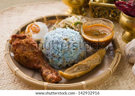 Traditional Malaysian food. Nasi kerabu is a type of nasi ulam, popular Malay rice dish. Blue color of rice resulting from the petals of butterfly-pea flowers. Asian cuisine.  - stock photo