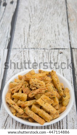 Traditional Malaysian snack locally known as Kuih Gunting or Spices Crunch, deep fried pieces of dough with spices in wooden bowl over wooden background