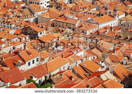 Traditional Mediterranean Old Town houses with red tiled roofs and rocky green idyllic island in background, Dubrovnik, Dalmatia, Croatia, Europe. Beautiful travel architecture photo texture. - stock photo