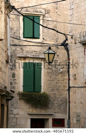 Traditional mediterranean street with stone houses, picturesque windows and retro lamps. In Trogir, Croatia. Trogir is popular touristic destination and UNESCO World Heritage Site.