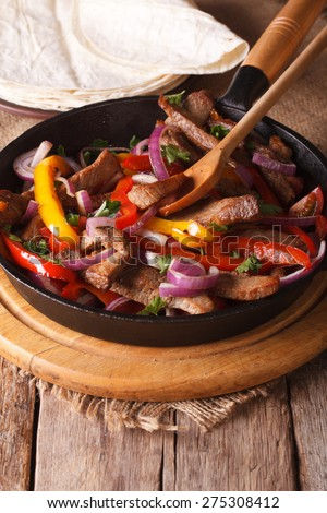 Traditional Mexican fajitas close up on the table. Vertical rustic style
