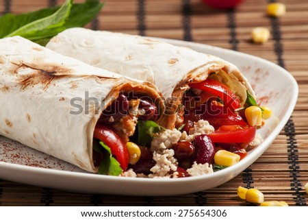 Traditional Mexican food, burritos with meat and beans, selective focus - stock photo