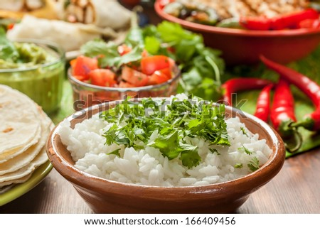 traditional mexican food: cilantro and lime rice, chicken fajitas, fajita peppers, burritos, tortillas, guacamole and salsa - stock photo