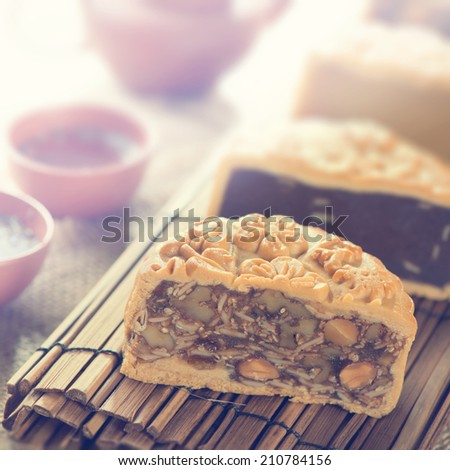 Traditional mooncakes on table setting with teacup. Retro vintage style Chinese mid autumn festival foods. The Chinese words on the mooncakes means assorted fruits nuts, not a logo or trademark. - stock photo