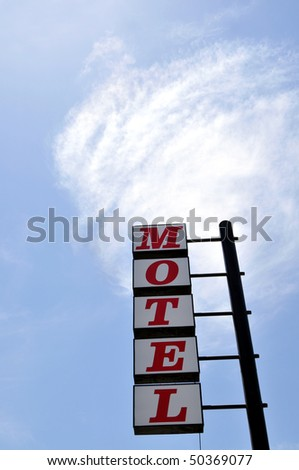 "Traditional ""Motel"" sign against a cloud in the sky"