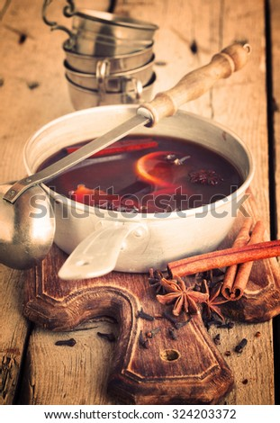 Traditional mulled wine with spices.Christmas or winter warming drink. Honey, orange, cinnamon sticks, cloves ,ginger,cardamom and sugar.Toned Vintage Christmas Composition.selective focus - stock photo