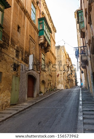 Traditional narrow street and old houses in Malta. Maltese architecture in Valletta, Malta - stock photo