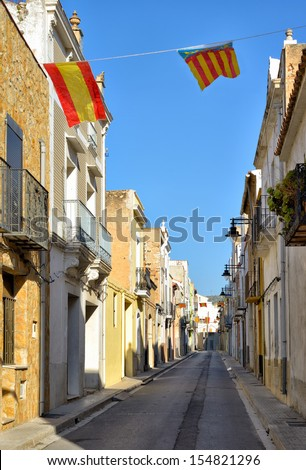 Traditional narrow street in historical center of Alcala de Xivert city in Valencia province, Spain decorated with flags of Spain and Valencia. - stock photo