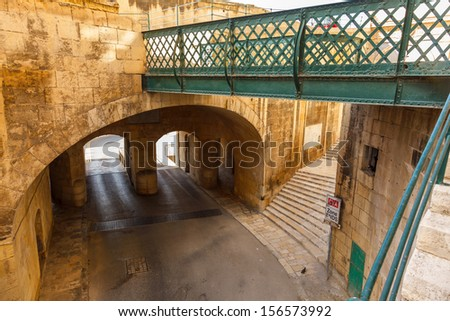 Traditional narrow street, old houses, arch, tunnel and footbridge in Malta. Maltese architecture in Valletta, Malta - stock photo