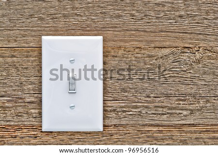 Traditional North American toggle white house electric light switch in ON position on aged old wood wall - stock photo