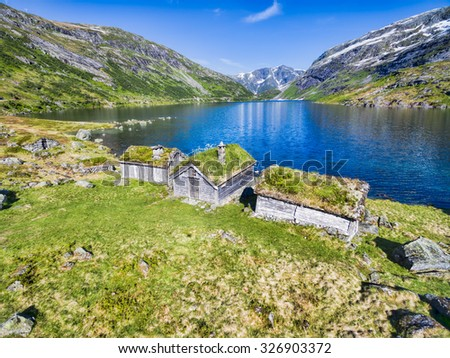 Traditional norwegian huts by picturesque lake surrounded by mountains in Gaularfjellet mountain pass in Norway - stock photo