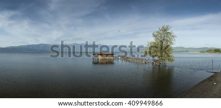 Traditional old fishing hut and wooden pier at Lake Dojran - panoramaTree in the water  which  just to be at the shoreline and beautiful cloudy sky - stock photo