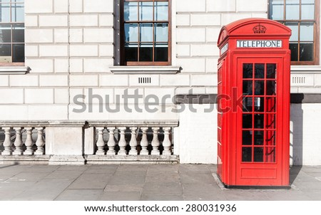 Traditional old-style UK red phone box set against a beige government building in central London. - stock photo