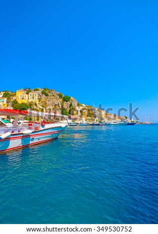 traditional old transportation boat docked in the main port of Symi island in Greece - stock photo