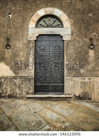 Traditional old vintage iron door and grunge wall in Tuscany, Italy, Europe. - stock photo