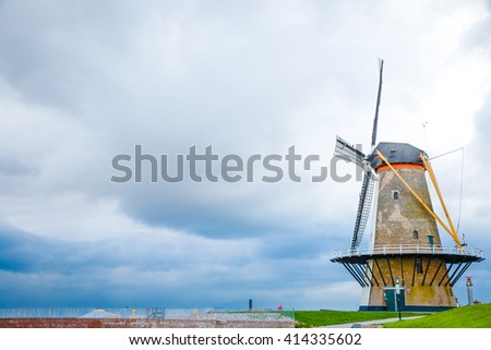 Traditional Orange Windmill (Oranjemolen) on the dike in Vlissingen, The Netherlands. Dark clouds are approaching. - stock photo