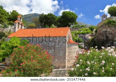 Traditional orthodox church hidden beyond Mediterranean vegetation, Montenegro - stock photo