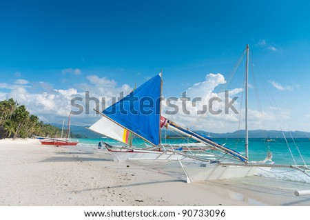 traditional paraw sailing boats on the famous white beach on Boracay island, Philippines