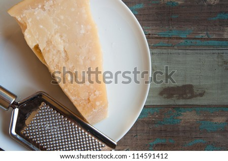 Traditional parmesan cheese on a white plate with a hand grater on a rustic wooden tabletop. - stock photo