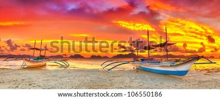 Traditional philippine boat bangka at sunset time - stock photo