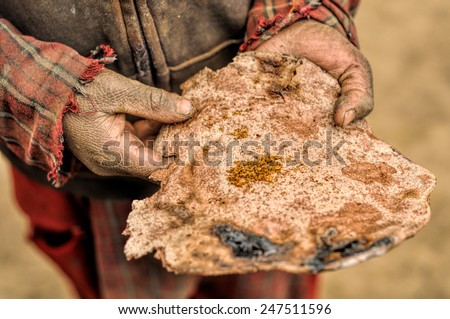 Traditional piece of thin nepalese bread in dirty hands