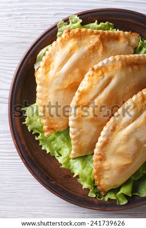 Traditional pies stuffed empanadas on a plate close-up. vertical view from above  - stock photo
