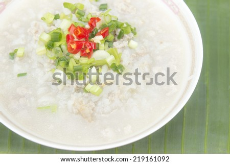 traditional pork porridge rice gruel in bowl Placed on a banana
