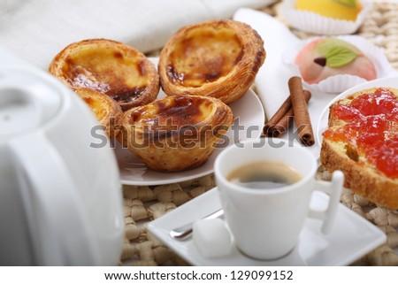 """traditional portuguese cakes - cream cake """"pasteis de nata"""" - shallow DOF - focus inside first cream cake - stock photo"""