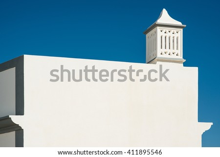 Traditional Portuguese chimney on top of a white building against great blue sky - stock photo