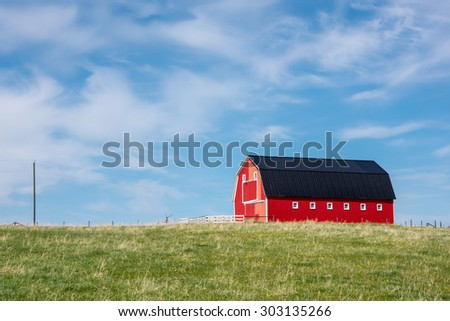 Traditional red barn with white trim in open pasture with blue sky & a few clouds - stock photo